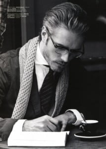 male model Benoit in scarf and coat writing at table